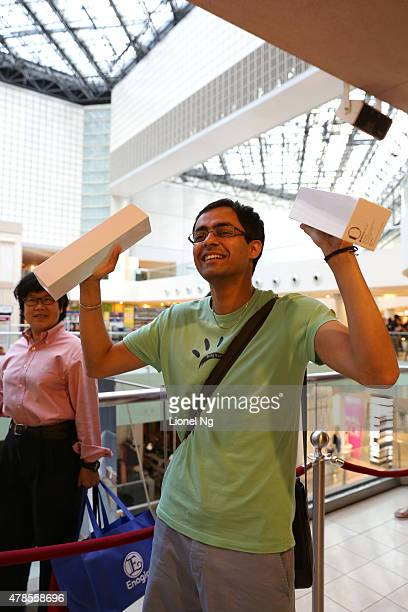 A customer poses with his newly purchased Apple Watch at an Apple retail store during the first day of the Apple Watch offical launch on June 26 2015...