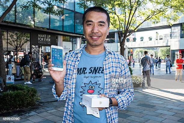 A customer poses with the new Apple iPhone 6s at Sanlitun Apple store on September 25 2015 in Beijing China Apple launched the new iPhone 6s and...