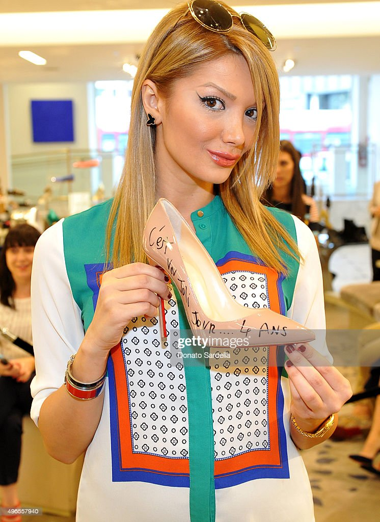 A customer poses with their signed shoe at designer Christian Louboutin's personal appearance and shoe signing at Saks Fifth Avenue Beverly Hills on November 10, 2015 in Beverly Hills, California