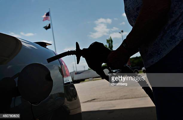 A customer prepares to fuel her vehicle at a Road Ranger gas station in Princeton Illinois US on Tuesday June 17 2014 Gasoline in the US climbed this...