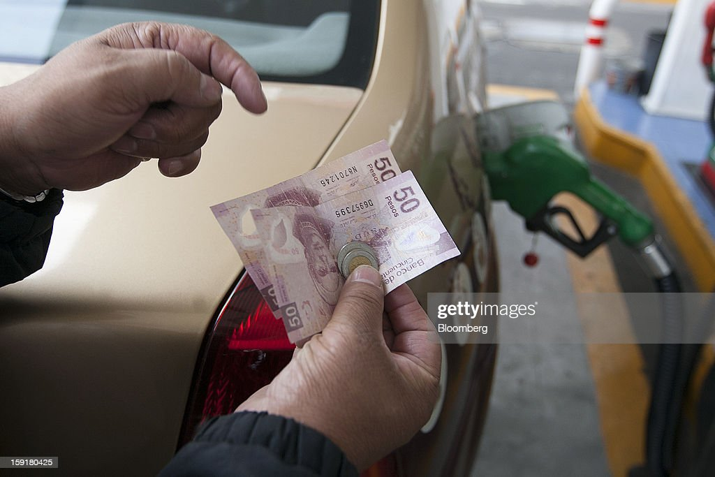 A customer prepares to pay after getting their tank filled with gasoline at a Pemex station in Mexico City, Mexico, on Tuesday, Jan. 8, 2013. Mexico's government is speeding up the removal of subsidies on gasoline and increasing local unleaded gasoline prices by 11 centavos in January, according to the Finance Ministry. Photographer: Susana Gonzalez/Bloomberg via Getty Images