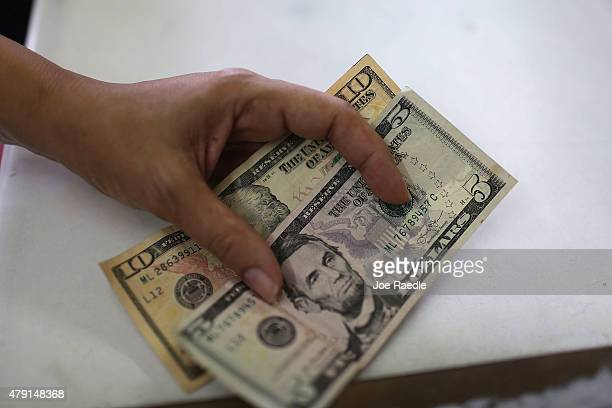 A customer prepares to pay for items in a grocery store on July 1 2015 in San Juan Puerto Rico The island's residents are dealing with increasing...
