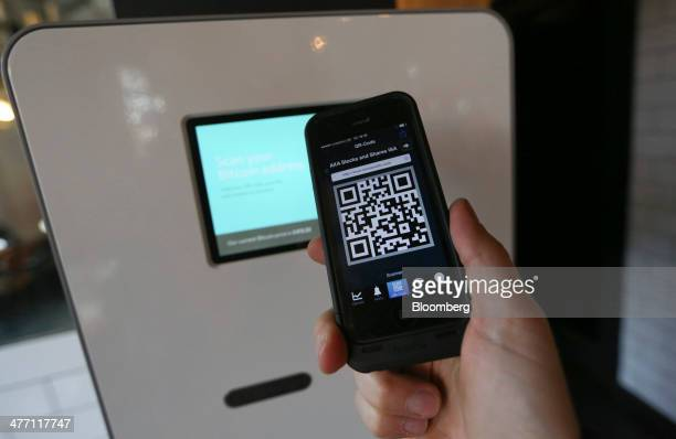 A customer prepares to scan a QR code reader to access a Bitcoin automated teller machine in this arranged photograph taken at the Old Shoreditch...