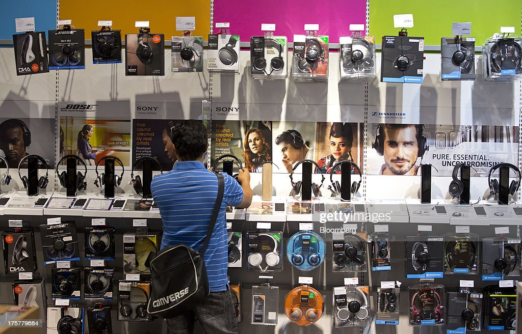 A customer prepares to try a pair of Sony Corp. headphones inside a Currys and PC World 2 in 1 store, operated by Dixons Retail Plc, at the Westfield Stratford City retail complex in London, U.K., on Thursday, Aug. 8, 2013. U.K. consumer confidence rose to the highest in more than three years as Britons' optimism about the economic outlook improved. Photographer: Simon Dawson/Bloomberg via Getty Images