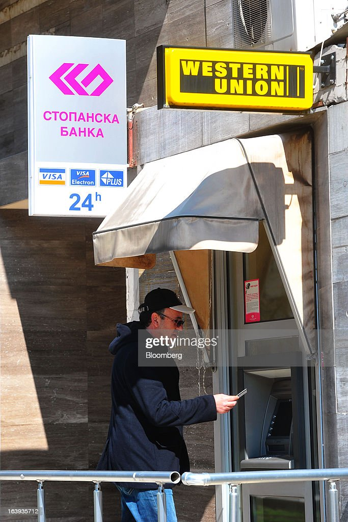 A customer prepares to use an automated teller machine (ATM) operated by Stopanska Banka near a Western Union sign in central Skopje, Macedonia, on Sunday, March 17, 2013. Macedonia's economy contracted by a real 0.3% on the year in 2012, compared to a growth of 2.8% a year earlier, an estimate released by the country's statistics office showed. Photographer: Oliver Bunic/Bloomberg via Getty Images