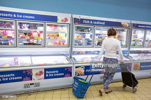 A customer pulls a blue plastic shopping basket branded with the Aldi name as they walk through the shopping aisles inside an Aldi supermarket store...