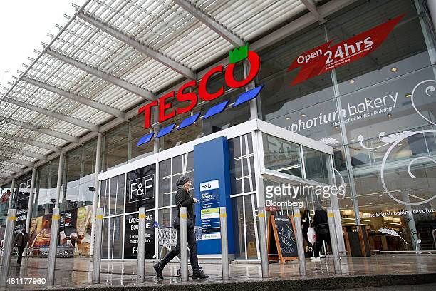 A customer pulls a shopping cart as she prepares to enter a Tesco supermarket store operated by Tesco Plc in the Kensington district of London UK on...