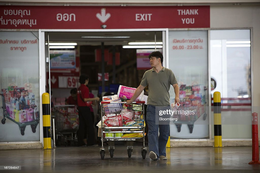 A customer pulls a shopping cart full of groceries as he leaves a Makro store, operated by Siam Makro Pcl, in Bangkok, Thailand, on Tuesday, April 23, 2013. Billionaire Dhanin Chearavanont's CP All Pcl, Thailand's 7-Eleven chain, offered to pay about $6.6 billion for discount retailer Siam Makro Pcl in the biggest takeover announced in Asia this year. Photographer: Brent Lewin/Bloomberg via Getty Images