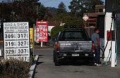 A customer pumps gas into his truck at a Gas Shop gas station on October 27 2014 in San Anselmo California Gas prices have fallen to their lowest...