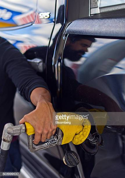 A customer pumps Sunoco gasoline into his truck at a Stripes convenience store in Corpus Christi Texas US on Thursday Jan 7 2016 Crude oil slid...