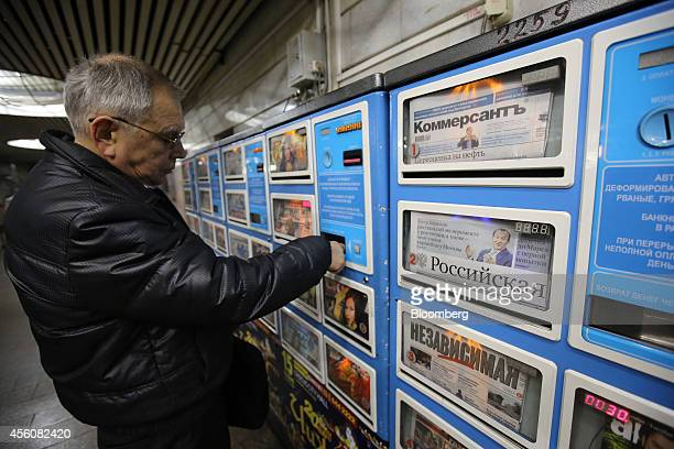 A customer purchases a newspaper from a vending machine which also displays copies of Kommersant Rossiyskaya and Nezavisimaya news publications right...