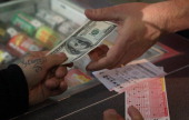 A customer purchases a Powerball lottery ticket at a 7Eleven store on November 28 2012 in Chicago Illinois Jim Bayci who owns the store estimates...