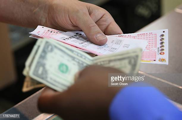 A customer purchases a Powerball lottery ticket at a 7Eleven store on August 7 2013 in Chicago Illinois The Powerball jackpot for tonight's drawing...