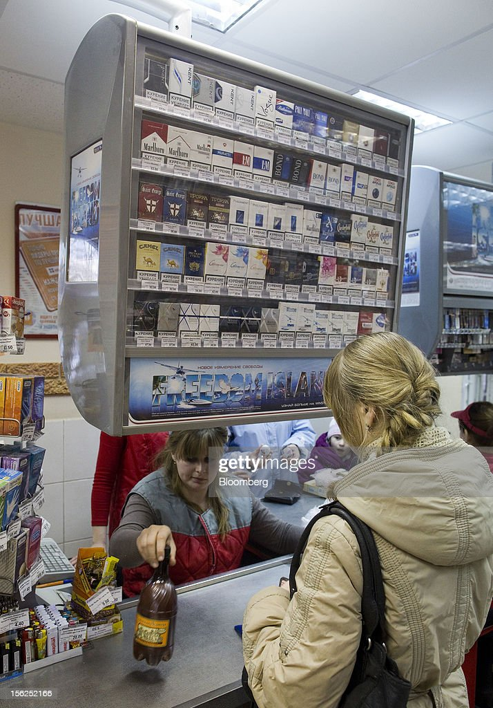 A customer purchases good from the sales counter of a local supermarket displaying cigarettes for sale in Suzdal, Russia, on Sunday, Nov. 11, 2012. Russia has one of the world's lowest retirement ages, set in 1932 during the Stalin era. Photographer: Andrey Rudakov/Bloomberg via Getty Images