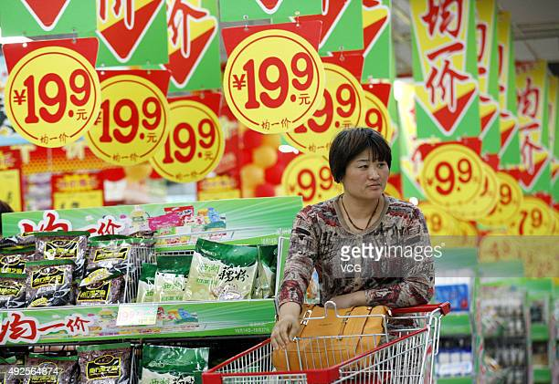 A customer purchases goods at a supermarket on October 14 2015 in Huaibei Anhui Province of China China's Consumer Price Index rose 16% in September...