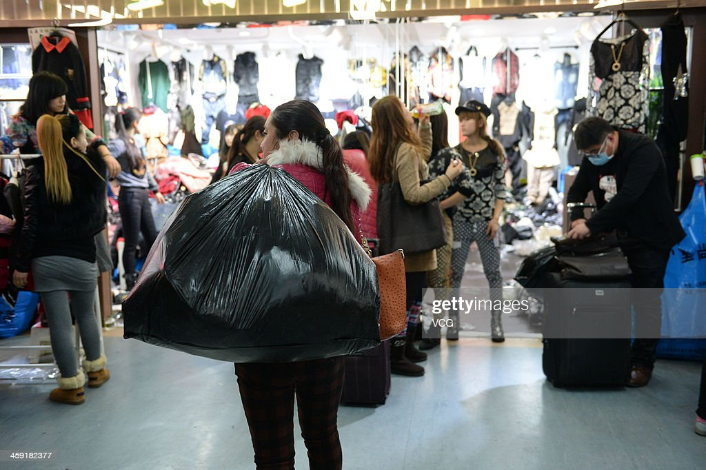 A customer purchases goods in the Zoo clothing market on December 23, 2013 in Beijing, China. The Zoo clothing market is a massive wholesale market actually comprises seven markets. This incredible indoor market, and the similarly laid out buildings around it, have mazes of shops and stalls with wonderfully inexpensive clothes, shoes, and accessories. A large garment wholesale market in Beijing is expected to move to Hebei province in 2014 to help ease heavy traffic in the Chinese capital.