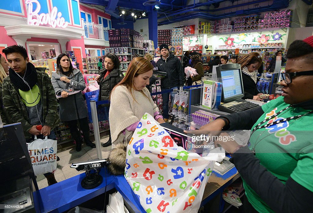 A customer purchases merchandise at a checkout counter at a Toys R Us Inc. store ahead of Black Friday in New York, U.S., on Thursday, Nov. 28, 2013. U.S. retailers will kick off holiday shopping earlier than ever this year as stores prepare to sell some discounted items at a loss in a battle for consumers. Photographer: Peter Foley/Bloomberg via Getty Images