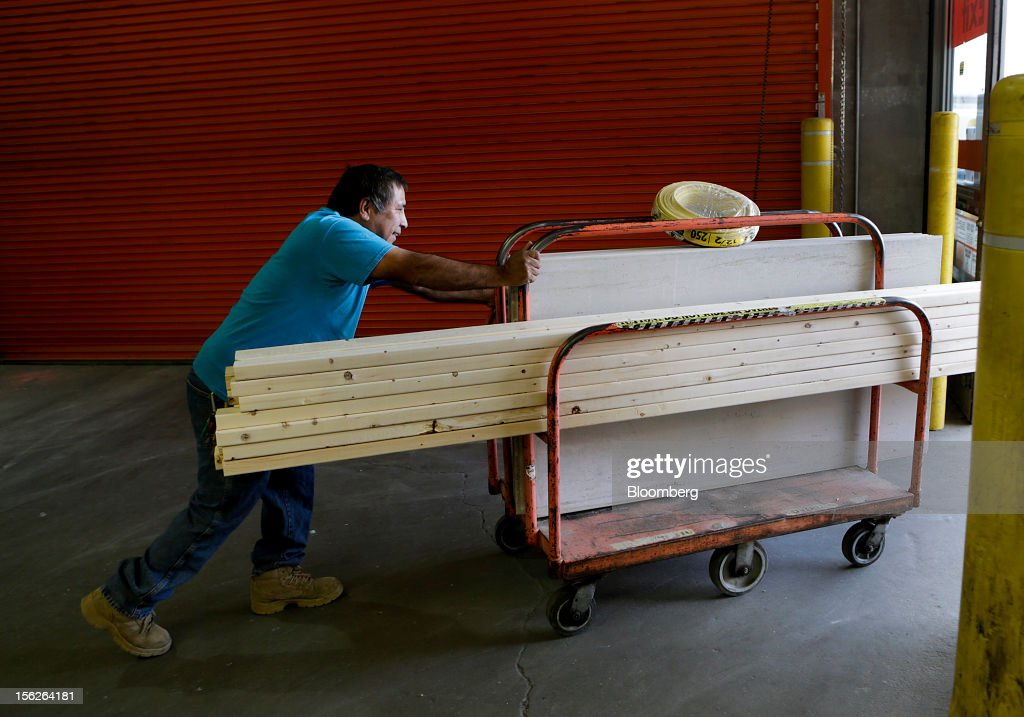 A customer pushes a cart with lumber and other supplies out of a Home Depot Inc. store in Washington, D.C., U.S., on Monday, Nov. 12, 2012. Home Depot Inc. is scheduled to release earnings data on Nov. 13. Photographer: Andrew Harrer/Bloomberg via Getty Images