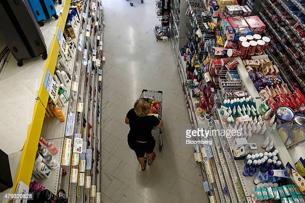 A customer pushes a shopping cart along a food aisle while shopping inside a local supermarket in Athens Greece on Friday July 3 2015 Shortages of...