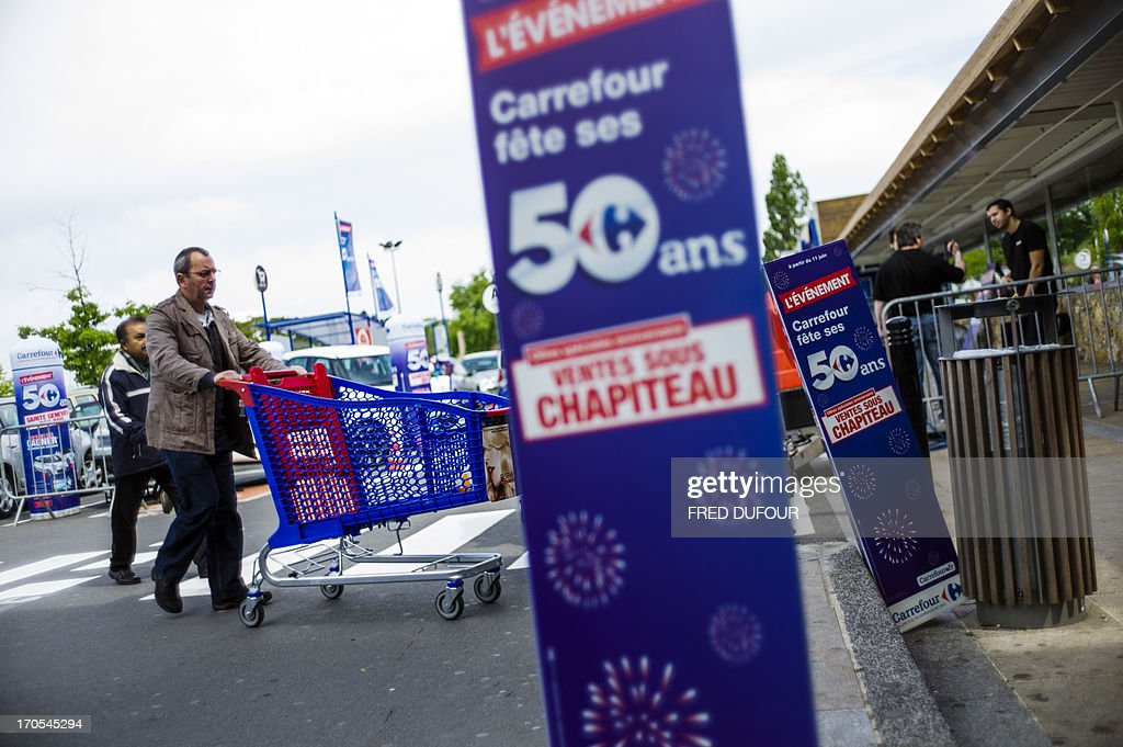 A customer pushes a shopping cart as he arrives at a Carrefour supermarket, on June 14, 2013 in Sainte-Geneviève-des-Bois, outside Paris. Installed in Sainte-Geneviève-des-Bois since fifty years, on June 15, 1963, this supermarket is the first of French giant retailer Carrefour group, but also the first in France.