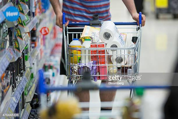 A customer pushes a shopping cart as he browses for goods inside a Tesco supermarket operated by Tesco Plc in London UK on Monday April 20 2015...