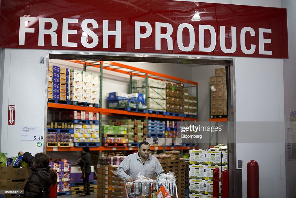 A customer pushes a shopping cart as others browse at a Costco Wholesale Corp. store in New York, U.S., on Monday, March 11, 2013. Costco is expected to release quarterly earnings results on March 12. Photographer: Victor J. Blue/Bloomberg via Getty Images