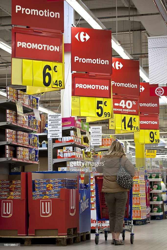 A customer pushes a shopping cart as she browses products on promotion inside a Carrefour SA supermarket in Portet sur Garonne, near Toulouse, France, on Tuesday, March 5, 2013. Carrefour's stock has risen 47 percent since Georges Plassat's arrival as chief executive officer, partially offsetting a 71 percent decline in the preceding five years. Photographer: Balint Porneczi/Bloomberg via Getty Images