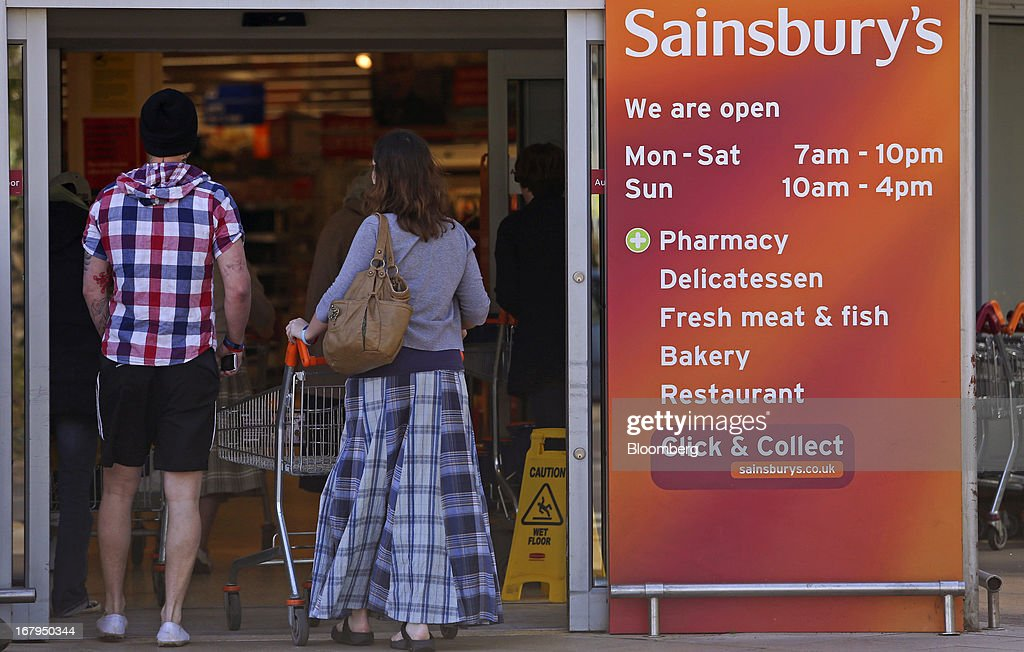 A customer pushes a shopping cart as she enters a Sainsbury's supermarket store, operated by J Sainsbury Plc, in Godalming, U.K., on Thursday, May 2, 2013. J Sainsbury Plc, the U.K.'s third-largest supermarket chain, will report full year results on May 8. Photographer: Chris Ratcliffe/Bloomberg via Getty Images