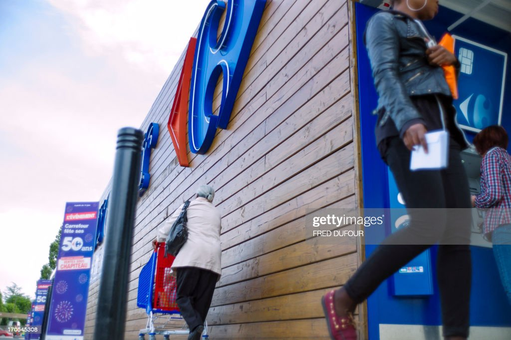 A customer pushes a shopping cart as she leaves a Carrefour supermarket, on June 14, 2013 in Sainte-Geneviève-des-Bois, outside Paris. Installed in Sainte-Geneviève-des-Bois since fifty years, on June 15, 1963, this supermarket is the first of French giant retailer Carrefour group, but also the first in France. AFP PHOTO / FRED DUFOUR