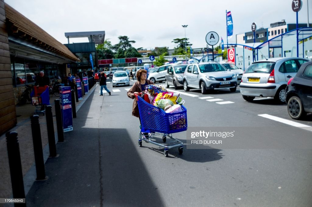 A customer pushes a shopping cart as she leaves a Carrefour supermarket, on June 14, 2013 in Sainte-Geneviève-des-Bois, outside Paris. Installed in Sainte-Geneviève-des-Bois since fifty years, on June 15, 1963, this supermarket is the first of French giant retailer Carrefour group, but also the first in France.