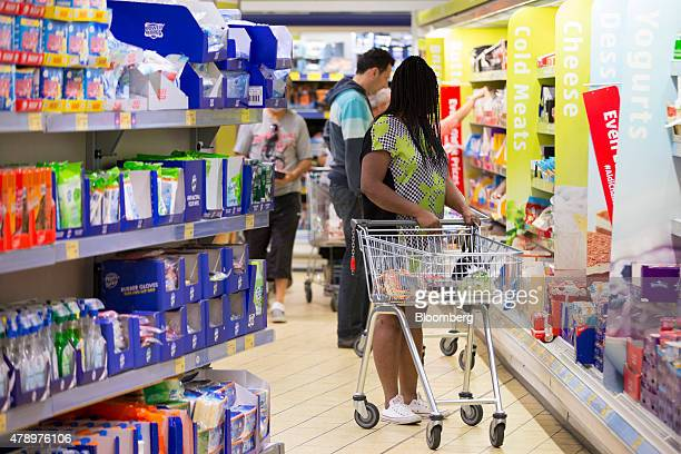A customer pushes a shopping cart as they walk through the shopping aisles inside an Aldi supermarket store in London UK on Monday June 29 2015 The...