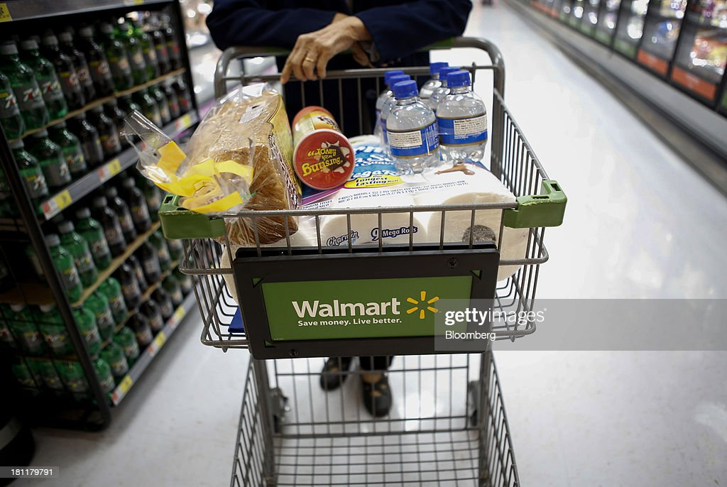 A customer pushes a shopping cart during the grand opening of a Wal-Mart Stores Inc. location in the Chinatown neighborhood of Los Angeles, California, U.S., on Thursday, Sept. 19, 2013. Wal-Mart Stores Inc. will phase out 10 chemicals it sells in favor of safer alternatives and disclose the chemicals contained in four product categories, the company announced Sept. 12. Photographer: Patrick T. Fallon/Bloomberg via Getty Images