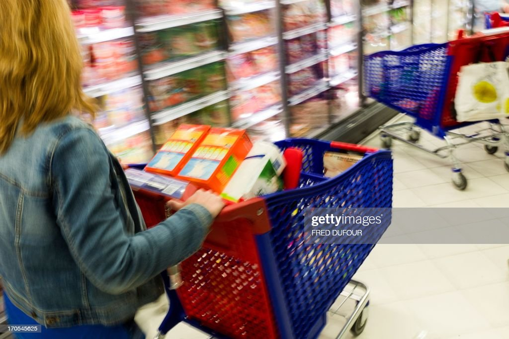 A customer pushes a shopping cart in a Carrefour supermarket, on June 14, 2013 in Sainte-Geneviève-des-Bois, outside Paris. Installed in Sainte-Geneviève-des-Bois since fifty years, on June 15, 1963, this supermarket is the first of French giant retailer Carrefour group, but also the first in France.