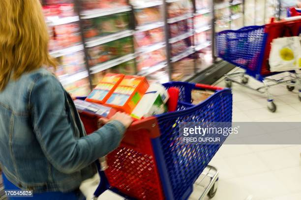 A customer pushes a shopping cart in a Carrefour supermarket on June 14 2013 in SainteGenevièvedesBois outside Paris Installed in...