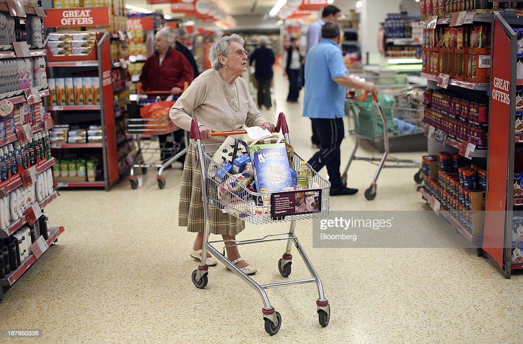 A customer pushes a shopping cart laden with goods as she browses the aisles of a Sainsbury's supermarket store, operated by J Sainsbury Plc, in Godalming, U.K., on Thursday, May 2, 2013. J Sainsbury Plc, the U.K.'s third-largest supermarket chain, will report full year results on May 8. Photographer: Chris Ratcliffe/Bloomberg via Getty Images