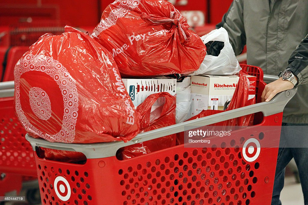 A customer pushes a shopping cart laden with merchandise at a Target Corp. store opening ahead of Black Friday in Chicago, Illinois, U.S., on Thursday, Nov. 28, 2013. U.S. retailers will kick off holiday shopping earlier than ever this year as stores prepare to sell some discounted items at a loss in a battle for consumers. Photographer: Patrick T. Fallon/Bloomberg via Getty Images