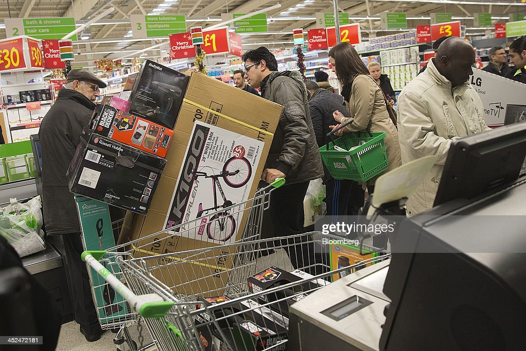 A customer pushes a shopping cart loaded with electronic goods and a bicycle through the self-serve check out desks during a Black Friday discount sale inside an Asda supermarket in Wembley, London, U.K., on Friday, Nov. 29, 2013. Britons queued outside Asda supermarkets this morning and charged into stores when doors opened at 8 a.m. as the U.K. grocery chain took on the Black Friday mantle from U.S. owner Wal-Mart Stores Inc. Photographer: Simon Dawson/Bloomberg via Getty Images