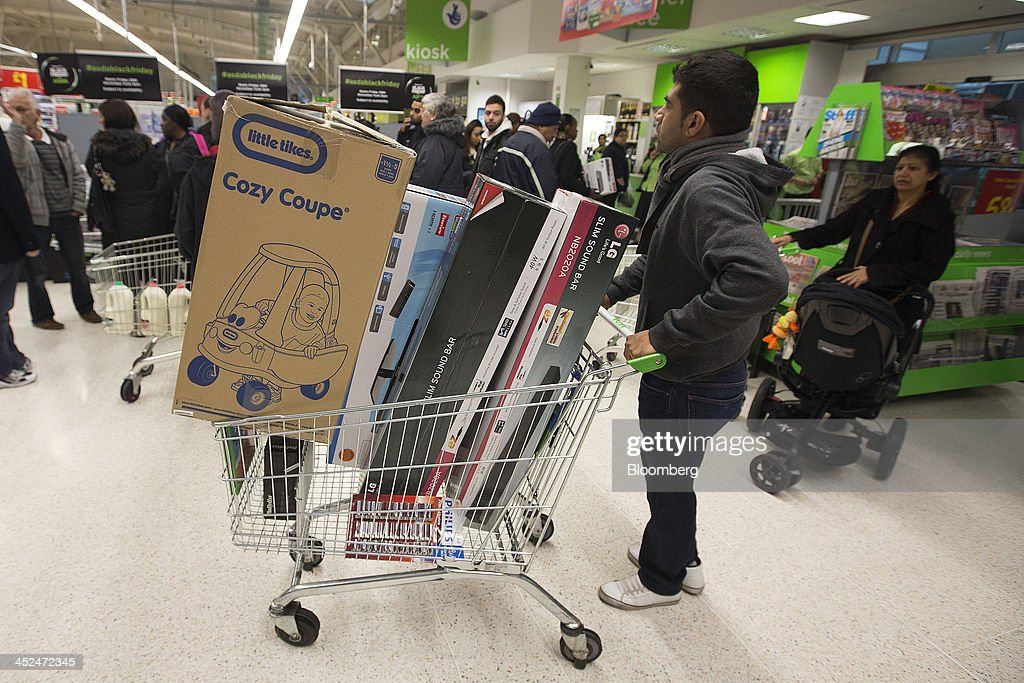 A customer pushes a shopping cart loaded with electronic goods and a Little Tikes children's toy during a Black Friday discount sale inside an Asda supermarket in Wembley, London, U.K., on Friday, Nov. 29, 2013. Britons queued outside Asda supermarkets this morning and charged into stores when doors opened at 8 a.m. as the U.K. grocery chain took on the Black Friday mantle from U.S. owner Wal-Mart Stores Inc. Photographer: Simon Dawson/Bloomberg via Getty Images