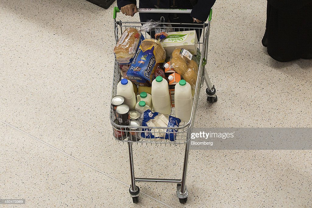 A customer pushes a shopping cart loaded with groceries including bread, milk and tinned goods as they shop for goods inside an Asda supermarket in Wembley, London, U.K., on Friday, Nov. 29, 2013. Britons queued outside Asda supermarkets this morning and charged into stores when doors opened at 8 a.m. as the U.K. grocery chain took on the Black Friday mantle from U.S. owner Wal-Mart Stores Inc. Photographer: Simon Dawson/Bloomberg via Getty Images