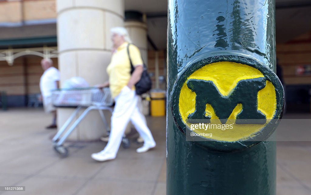 A customer pushes a shopping cart loaded with groceries past a logo-ed pillar outside a William Morrison Supermarkets Plc grocery store in Erith, U.K., on Wednesday, Sept. 5, 2012. Morrisons announced that 60 percent of store openings will be in southern England next year as it shifts attention from its northern heritage. Photographer: Chris Ratcliffe/Bloomberg via Getty Images