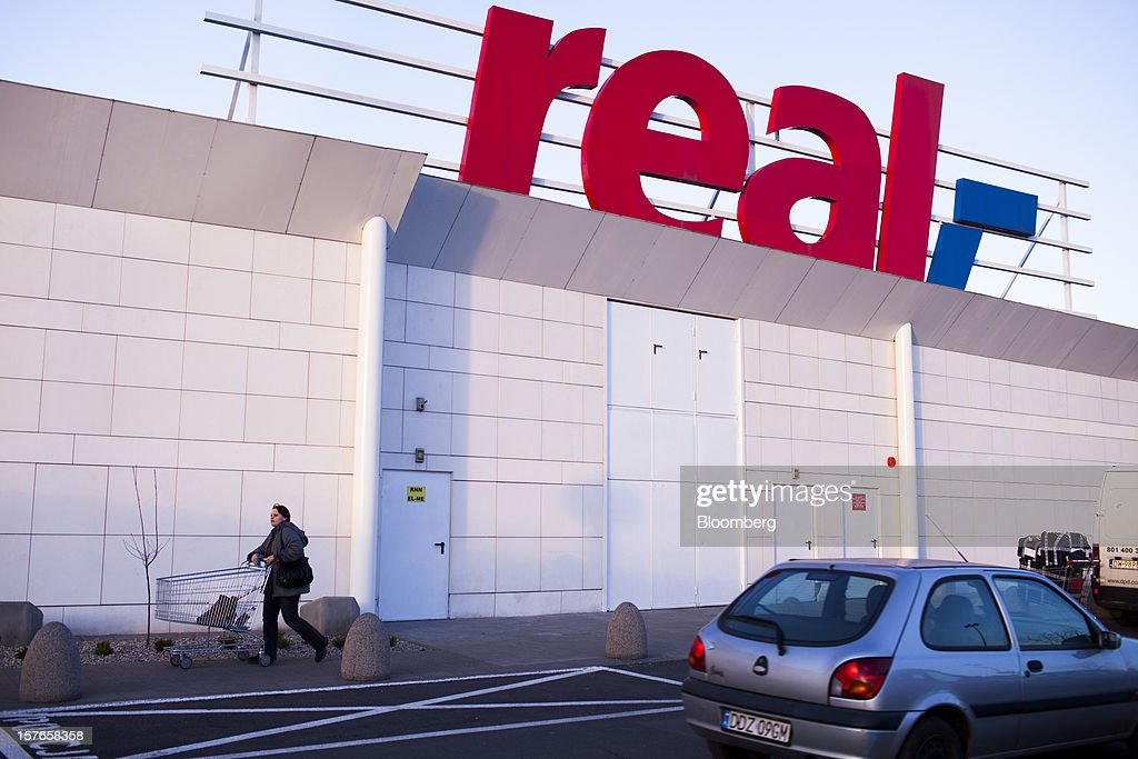 A customer pushes a shopping cart past a logo outside a Real supermarket in Wroclaw, Poland, on Wednesday, Dec. 5, 2012. Metro AG, Germany's biggest retailer, agreed to sell its Real grocery stores in eastern Europe to Groupe Auchan SA of France for 1.1 billion euros ($1.4 billion) in Chief Executive Officer Olaf Koch's first big deal since taking the helm. Photographer: Bartek Sadowski/Bloomberg via Getty Images
