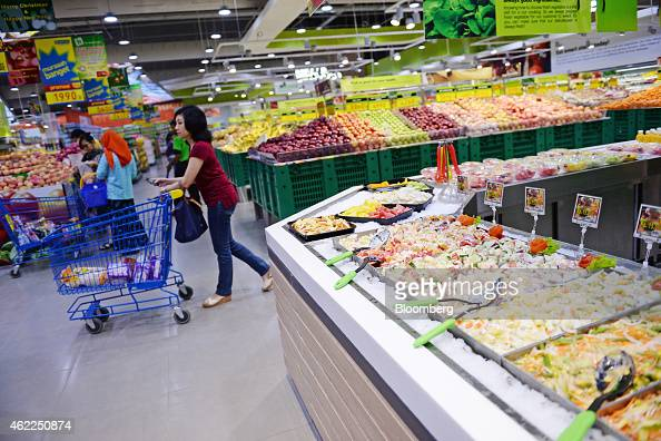A customer pushes a shopping cart past a salad counter at a Hypermart supermarket operated by PT Matahari Putra Prima in Karawaci Banten Indonesia on...