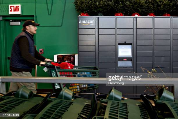 A customer pushes a shopping cart past a wall of Amazoncom Inc lockers a selfservice parcel delivery service inside the Lakeview Whole Foods Market...