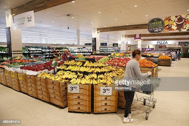 A customer pushes a shopping cart past bananas and other fruit at a Woolworths Ltd supermarket in Sydney Australia on Thursday Aug 27 2015 Woolworths...