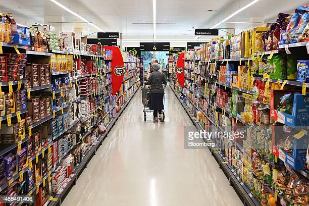 A customer pushes a shopping cart through a cereals and biscuits aisle at a Woolworths Ltd supermarket in Sydney Australia on Thursday Aug 27 2015...