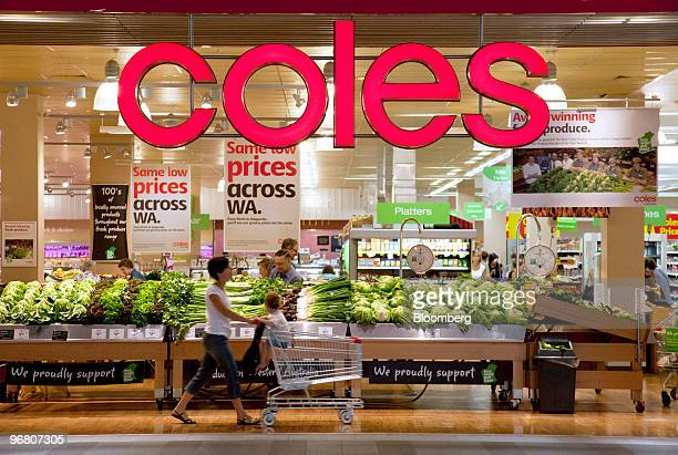 A customer pushes a shopping cart through a Coles Group Ltd supermarket in Perth Australia on Wednesday Feb 17 2010 Wesfarmers Ltd who owns retail...