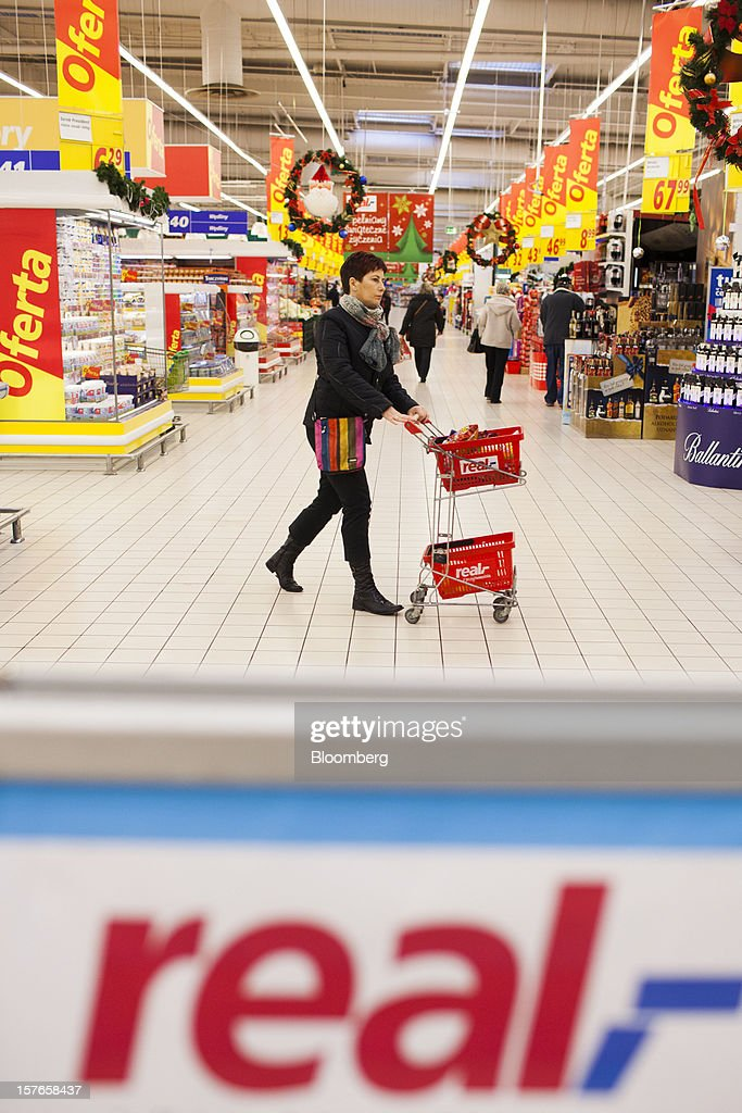 A customer pushes a shopping cart through the aisle inside a Real supermarket in Wroclaw, Poland, on Wednesday, Dec. 5, 2012. Metro AG, Germany's biggest retailer, agreed to sell its Real grocery stores in eastern Europe to Groupe Auchan SA of France for 1.1 billion euros ($1.4 billion) in Chief Executive Officer Olaf Koch's first big deal since taking the helm. Photographer: Bartek Sadowski/Bloomberg via Getty Images