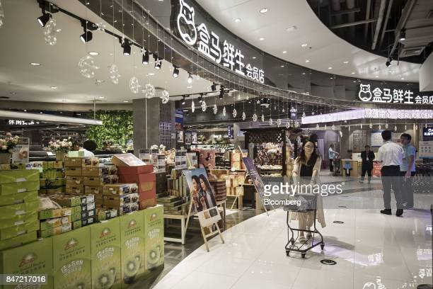 A customer pushes a shopping cart while browsing in an Alibaba Group Holding Ltd Hema Store in Shanghai China on Tuesday Sept 12 2017 Hema stores are...