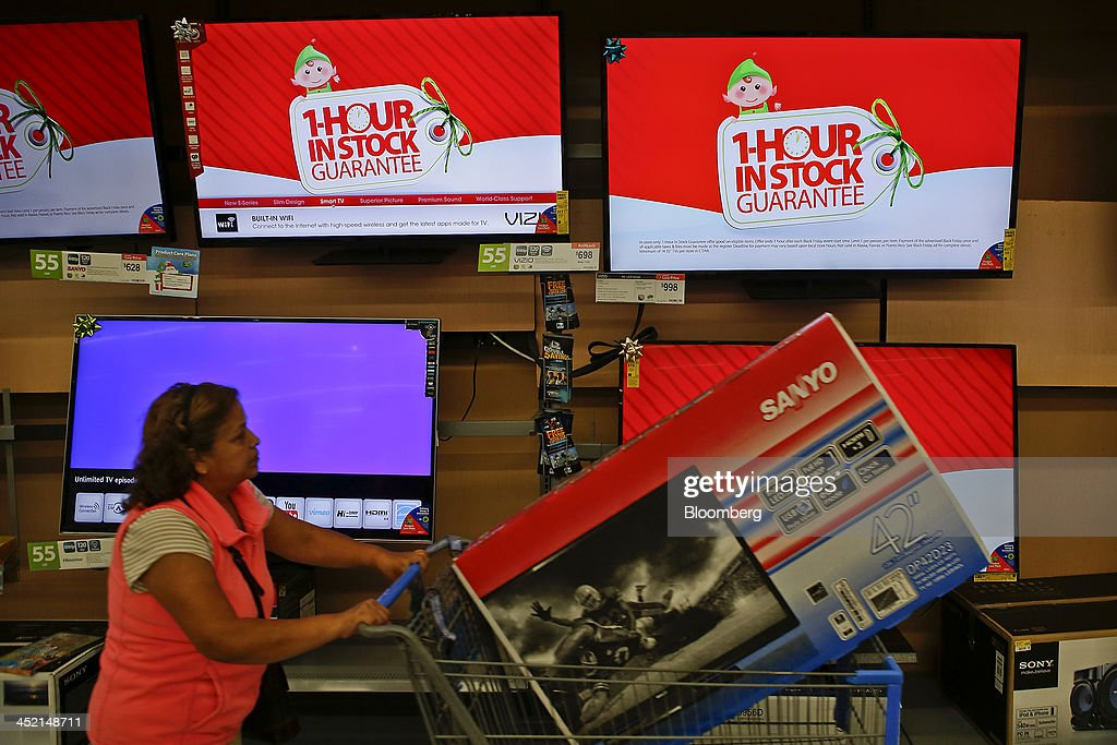 A customer pushes a shopping cart with a television as screens show advertisements for the Black Friday 1 Hour In Stock Guarantee at a Wal-Mart Stores Inc. location ahead of Black Friday in Los Angeles, California, U.S., on Tuesday, Nov. 26, 2013. Wal-Mart Stores Inc. said Doug McMillon, head of its international business, will replace Mike Duke as chief executive officer when he retires as the world's largest retailer struggles to ignite growth at home and abroad. Photographer: Patrick T. Fallon/Bloomberg via Getty Images