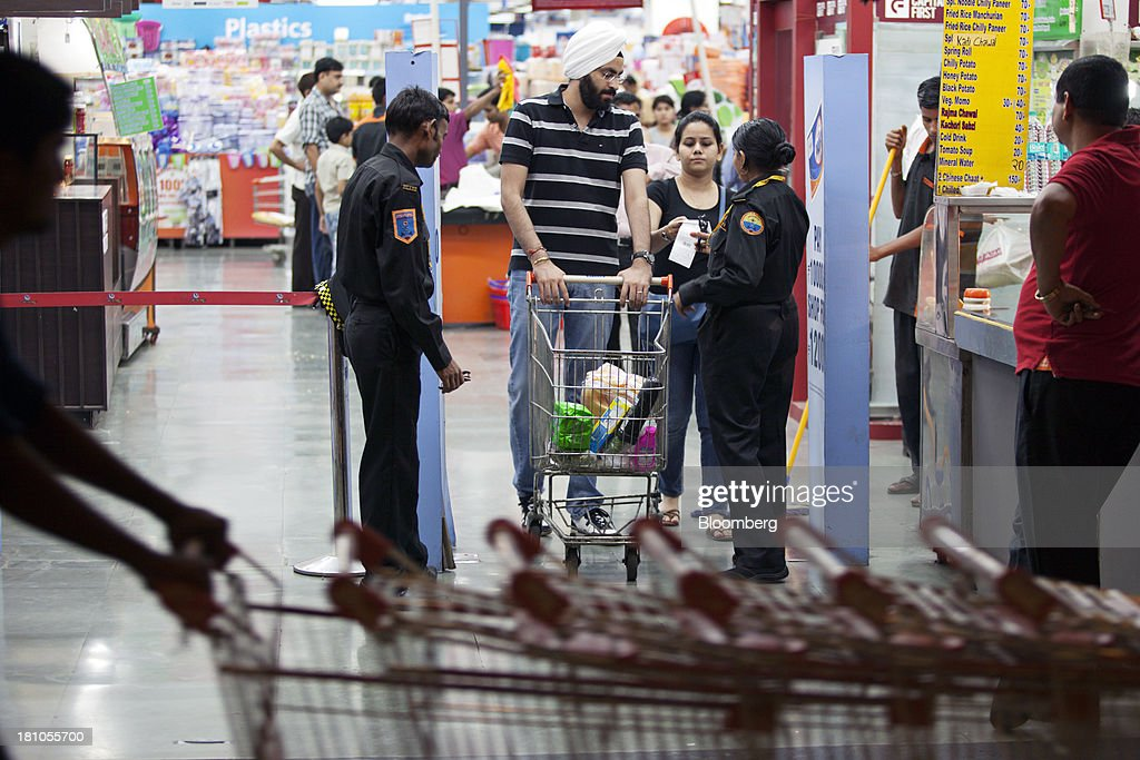A customer pushes a shopping trolley past security guards at the Big Bazaar Hypermarket store in Noida, India, on Monday, Sept. 9, 2013. Indias rupee fell, snapping the biggest four-day surge in 40 years, on concern slowing growth will deter inflows needed to reduce the current-account deficit. Photographer: Prashanth Vishwanathan/Bloomberg via Getty Images